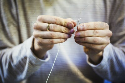 A craftsman's hands holding a leatherwork needle and threading cord through the eye of the needle.