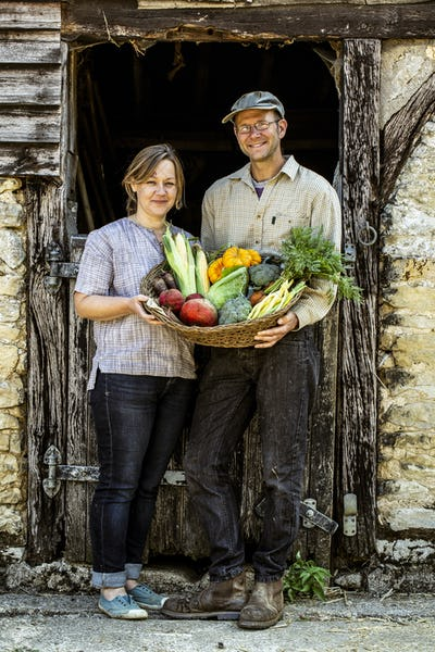 Smiling farmer and woman standing in barn door, holding basket with freshly harvested vegetables,