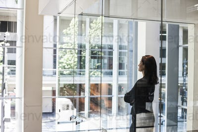 Businesswoman standing in a conference room window in a large business center.