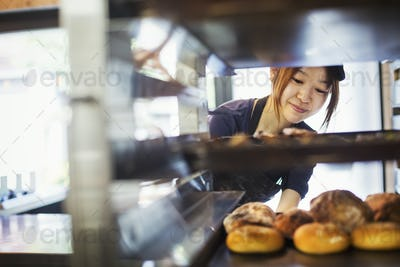Woman working in a bakery, placing large trays with freshly baked rolls on a trolley.