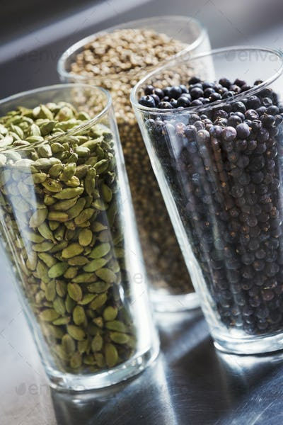 Close up of three glasses with spices, cardamom pods, coriander seeds and juniper berries.