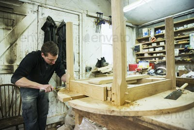 A man in a carpentry workshop, working on the edge of a new wooden table using a hammer.