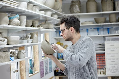 A man inspecting a clay pot, before firing. Shelves in a pottery studio full of pots, work in