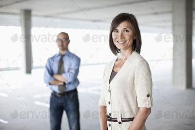 Caucasian businesswoman and Asian businessman standing in a large empty raw office space.