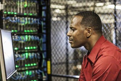 Black man technician doing diagnostic tests  on computer servers in server farm.