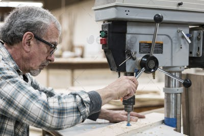 A senior man with glasses and beard in a woodworkers shop, using a machine.