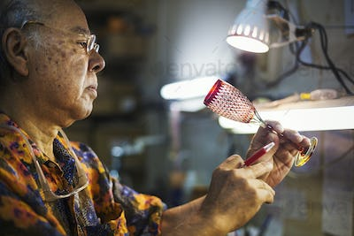 A senior craftsman at work in a glass maker's studio workshop, in inspecting red wine glass with cut