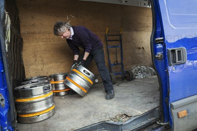 Man working in a brewery, loading metal beer kegs into a van.