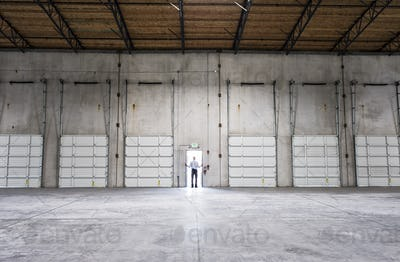 Man standing doorway of new warehouse waiting for the arrival of the first truck wiith new business.