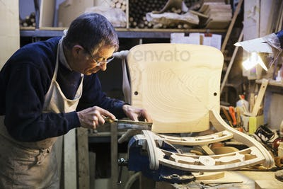 Man standing at a work bench in a carpentry workshop, working on a wooden chair with a small hand
