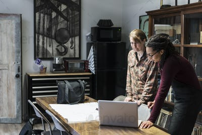 Two women gathered around table in office area of a metal workshop, looking at laptop.