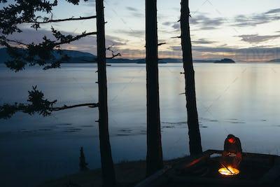 Man sitting by campfire at dusk, San Juan Islands in the distance, Washington, USA.