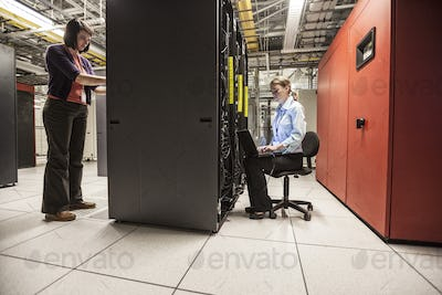 Caucasian women technicians working on computer servers in a server farm.