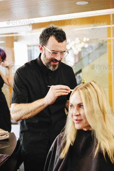 A hair colourist, a man using a paintbrush to cover sections of a woman's blonde hair.