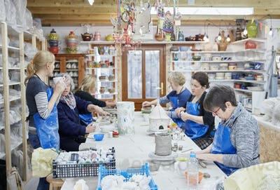 A group of people seated at a workbench in a pottery workshop, handbuilding clay objects. A woman