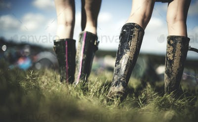 Low section rear view of two young women at a summer music festival wearing muddy Wellington boots.