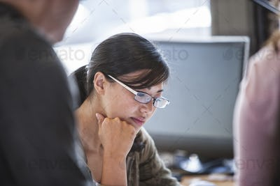 Asian woman leading an informal meeting in a creative office.