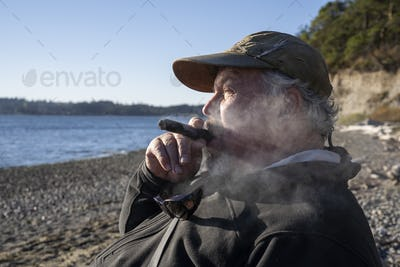 A fly fisherman enjoys a cigar and  takes a break from fly fishing for searun coastal cutthroat