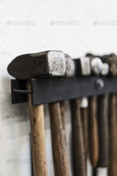 Close up of a selection of hammers hanging on a wall in a metal workshop.