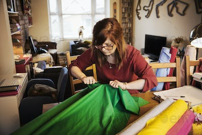 A woman ripping brightly coloured material on a tabletop in a workroom.