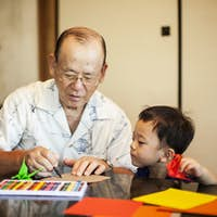 Japanese man and little boy sitting at a table, making Origami animals using brightly coloured