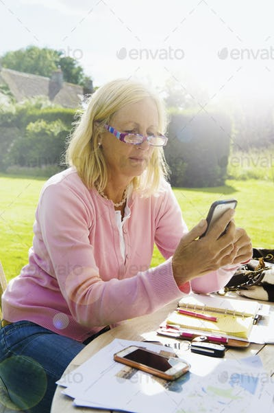 A blonde woman sitting in a garden at a table, with a smart phone and notebook, working outside.