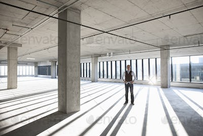 Asian businessman standing in a large empty raw office space.