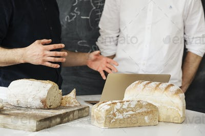 Close up of two bakers standing at a table, using a laptop computer, freshly baked bread.