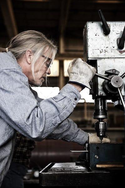 Caucasian man factory worker using a drill press in a sheet metal factory.
