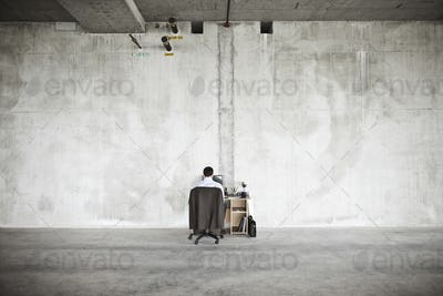 Businessman sitting at a small desk in a large empty raw office space.