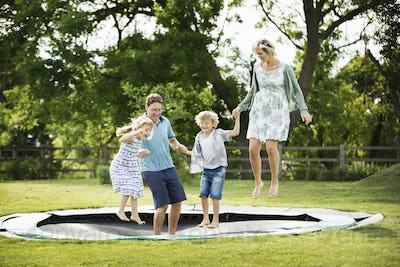 Man, woman, boy and girl holding hands, jumping on a trampoline set into the ground in a garden.