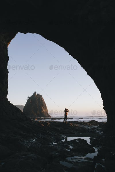 Man standing beneath sea cave at dusk, using binoculars at Hole-in-the-Rock, Rialto Beach, Olympic