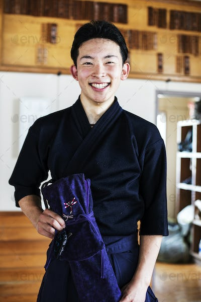 Male Japanese Kendo fighter standing in a gym, smiling at camera.