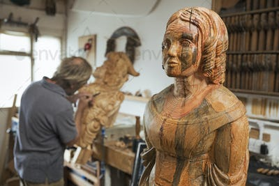 A craftsman working on a wooden ship's figurehead in a workshop using a chisel.  A finished object