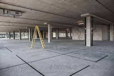 Large empty raw office space with a ladder set up on the floor.