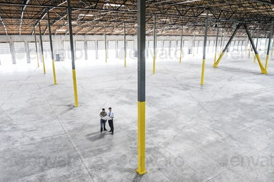Team of people checking out the new interior of an empty warehouse space.