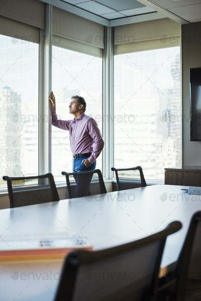 A man in a meeting room looking out of a window at an urban landscape.