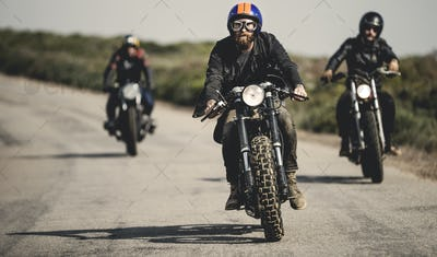 Three men wearing open face crash helmets and goggles riding cafe racer motorcycles along rural