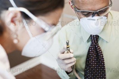 Closeup of a dentist and his assistant working on a patient in a dental office.
