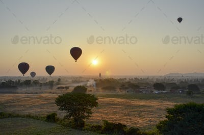 Hot air balloons over landscape with distant temples at sunset, Bagan, Myanmar.