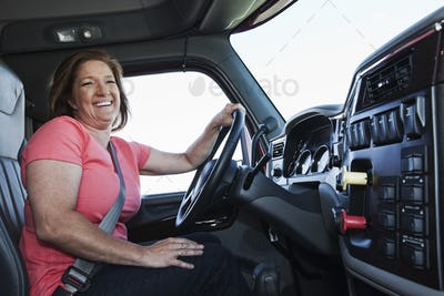 Caucasian woman driver in the cab of a  commercial truck.