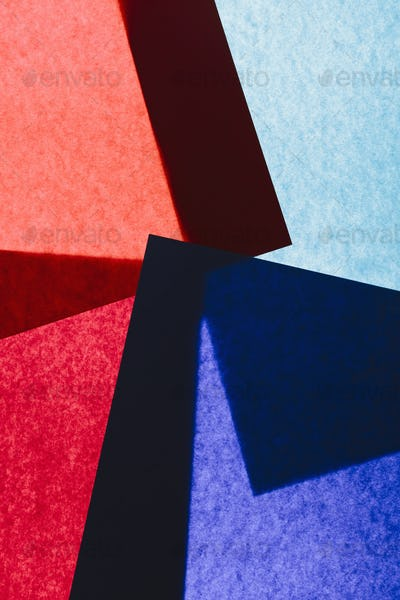 Overlapping pieces of multicolored construction paper on illuminated backdrop.
