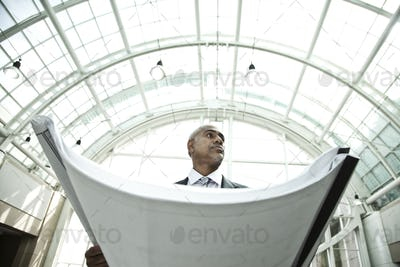 A businessman holding a large plan or architectural drawings standing under a glass domed ceiling,