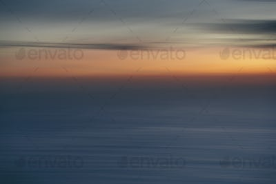 View out to sea over the ocean at dusk,  the sunset light on the horizon and calm undulating sea