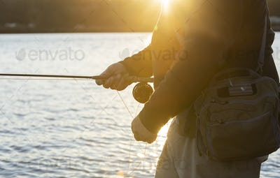 A closeup view of a the hands of a fly fisherman retrieving his line from a cast he made into salt