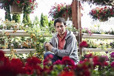 Young caucasian man employee of a garden center nursery.