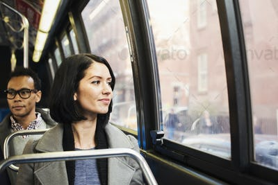 A young woman sitting on a train looking out of the window at an urban landscape, with a man sitting