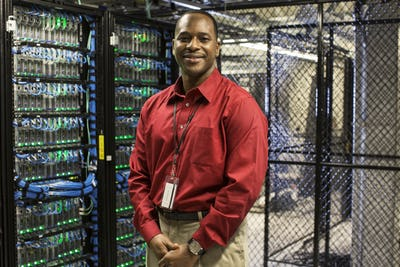 Black man technician in a computer server farm.