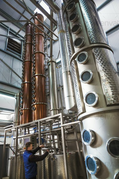 Tall copper distillery chambers in a brewery, brewing storage tanks in copper and steel. A man in