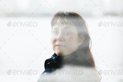 A woman with brown hair and a fringe, wearing a scarf at her neck, looking through a window.